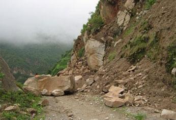Carretera bloqueada por derrumbe de piedrasy rocas.
